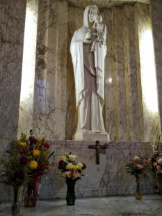 The roses were brought into the church and placed in a green vase by the large Mary statue
